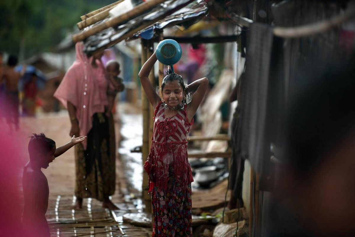 A young girl takes a shower using collected rain water at the Kutupalong camp, on July 19, 2018.