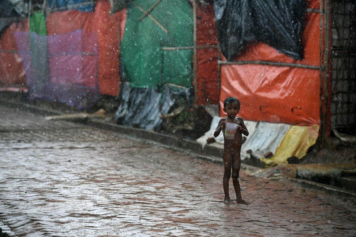 A child collects water in the pouring rain at Kutupalong camp, on July 19, 2018.