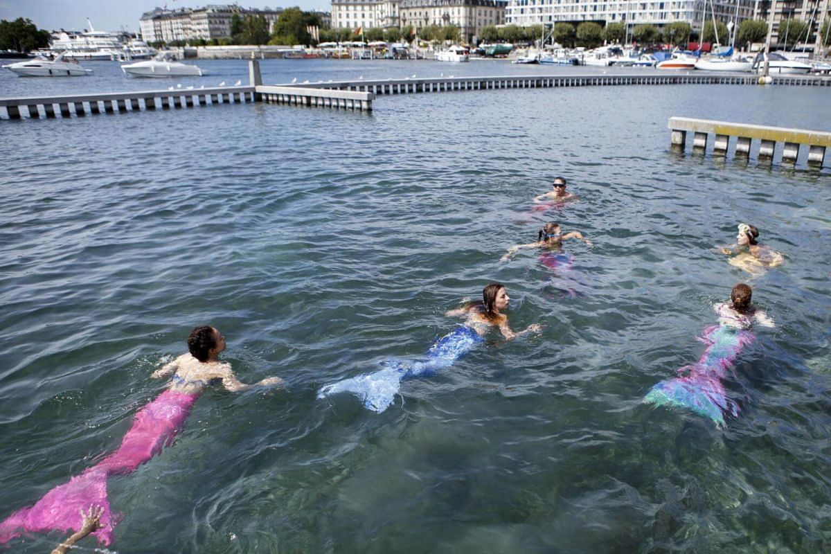 Women dressed as mermaids swim into the lake of Geneva, during a Mermaiding initiation at the Bains des Paquis, in Geneva, Switzerland, on Aug 11, 2018.