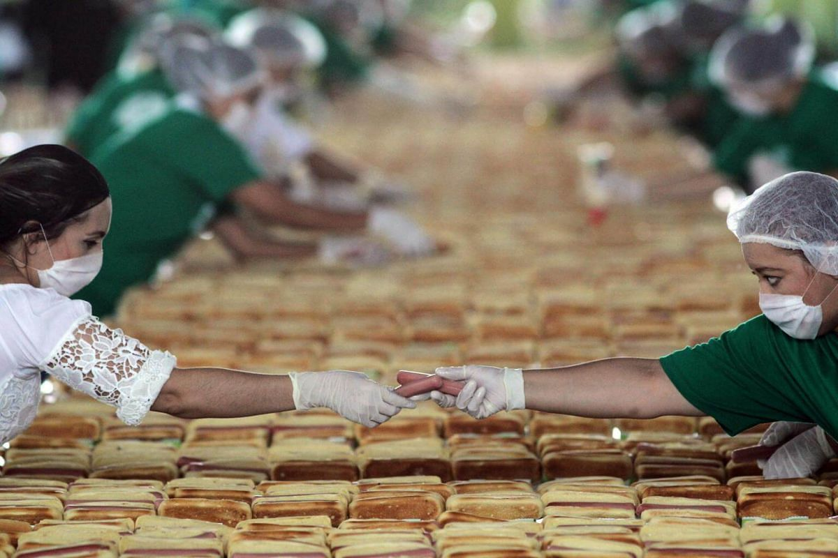 People prepare hundreds of hot dogs in an attempt to break the Guinness record of the longest hot dog line in Guadalajara, Jalisco State, on Aug 12, 2018.