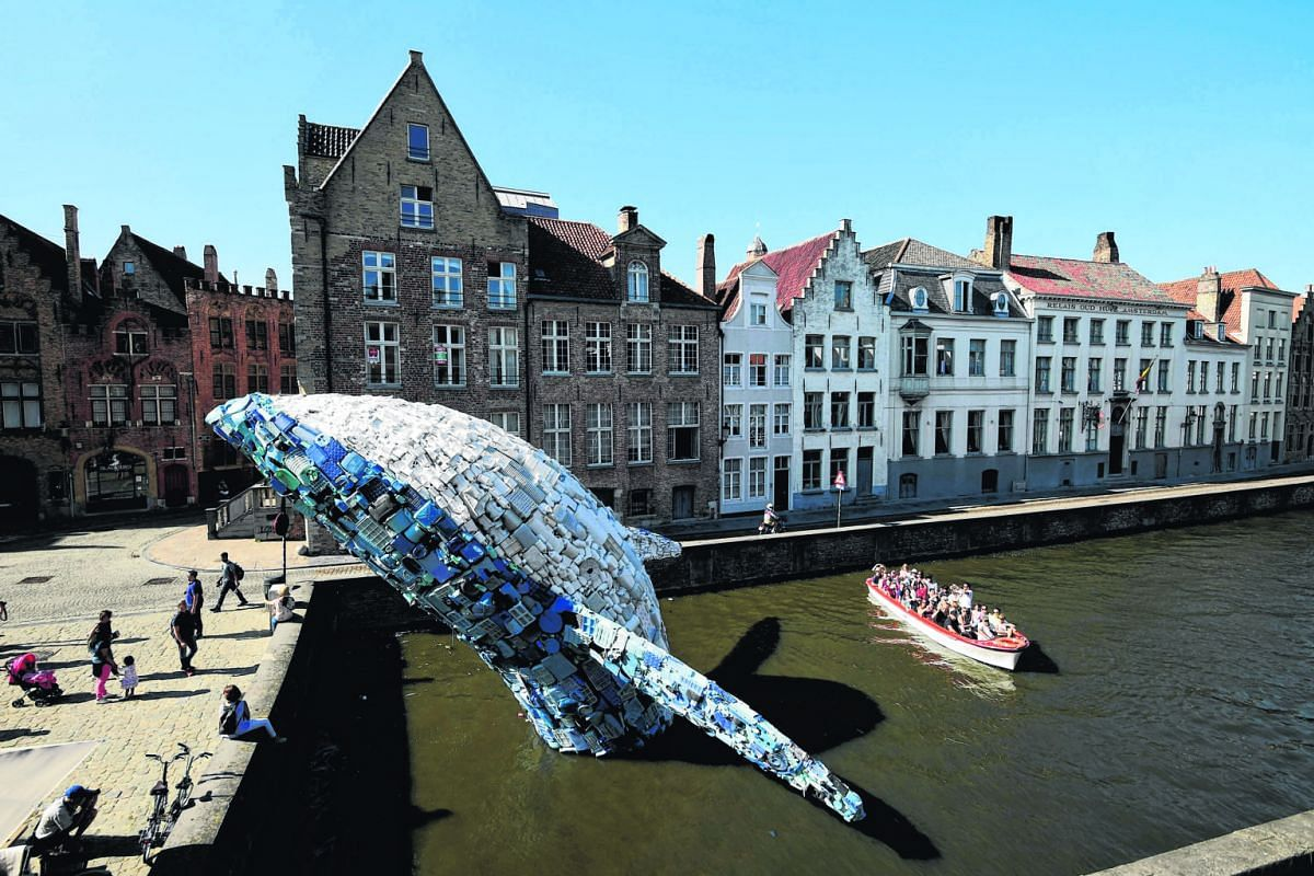 Left: A 10m installation depicting a whale - made up of five tonnes of plastic waste pulled from the Pacific Ocean - on display in Brugges, Belgium, last month. Below: A gigantic heap of plastic bottles piling up at a junkyard in Chandigarh, India, i