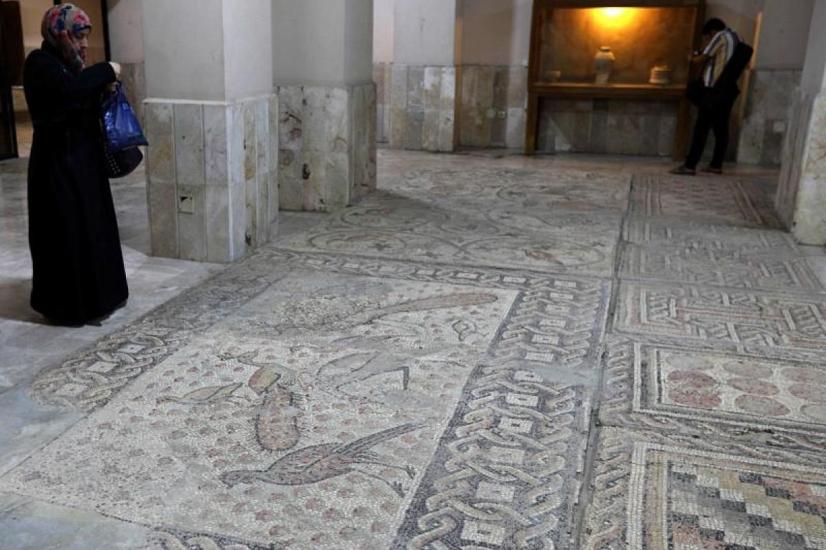A Syrian woman takes pictures of mosaic on the floor of the Idlib Museum after it reopened on Aug 13, 2018 in the northern Syrian city of Idlib. The antiquities museum in Syria's rebel-held province of Idlib , said to house one of the world's oldest
