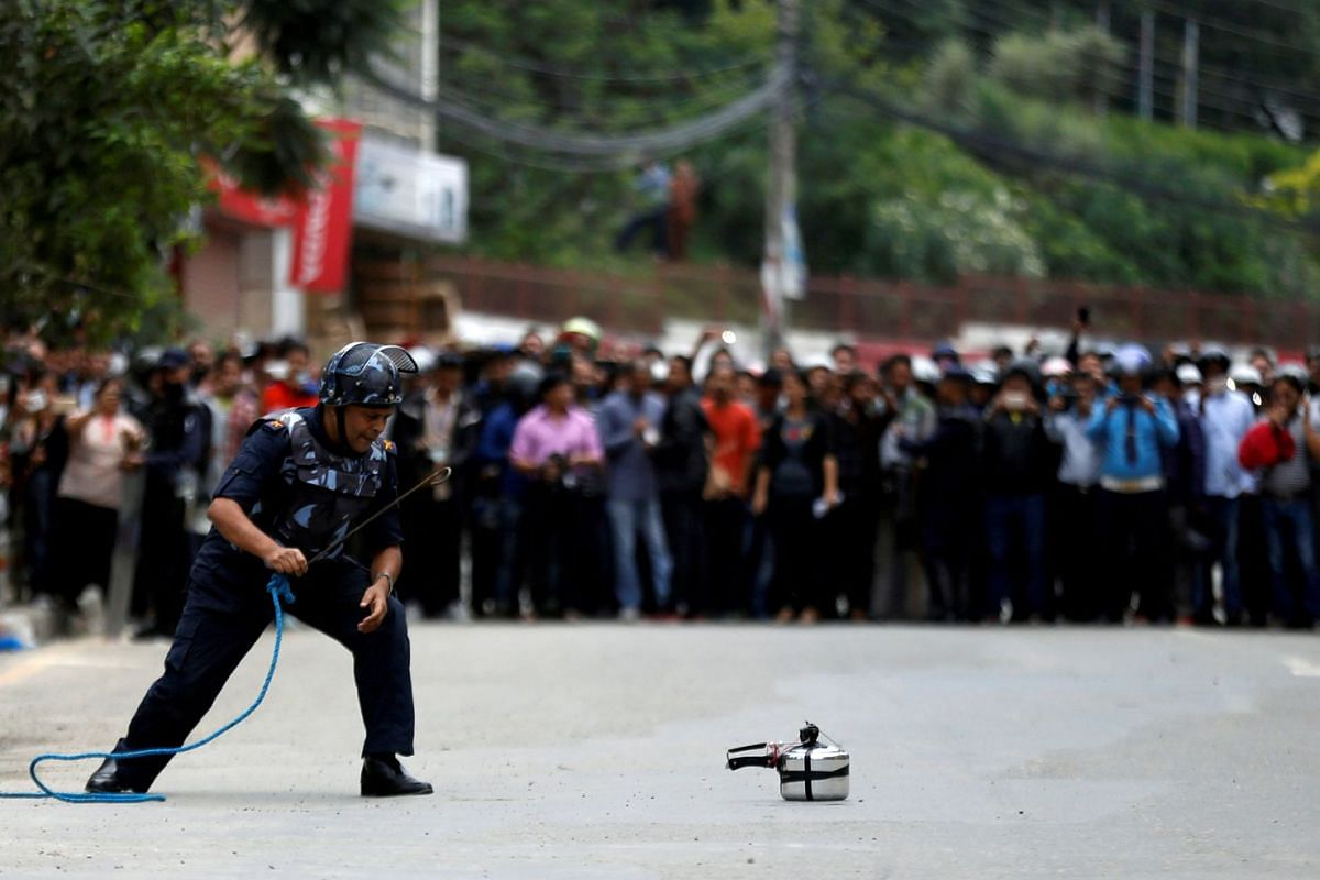 A member of Nepalese police checks a pressure cooker suspected of being an improvised bomb during a bomb scare in Lalitpur, Nepal August 14, 2018. The scare was later found to be a false alarm.