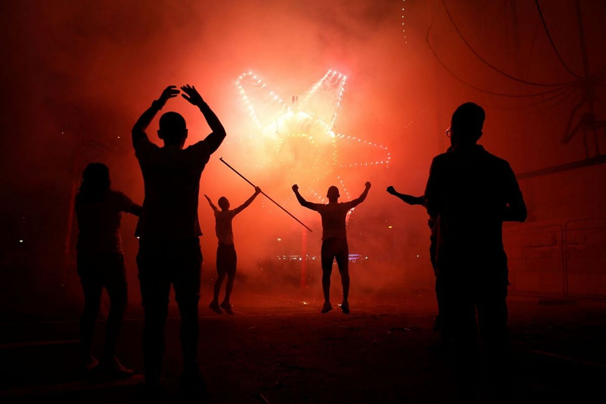 Enthusiasts celebrate during a mechanised ground fireworks display during week-long celebrations marking the feast of the Assumption of Our Lady in Mosta, Malta early August 15, 2018.