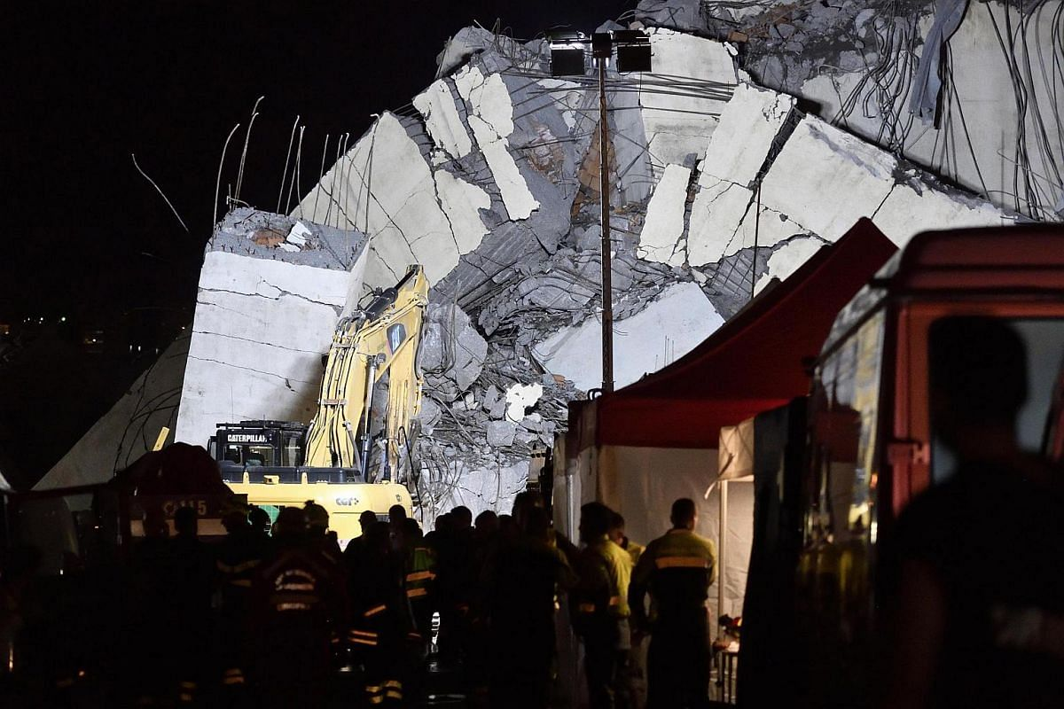 Rescuers work into the night at the site of the collapsed Morandi Bridge, on Aug 14, 2018.