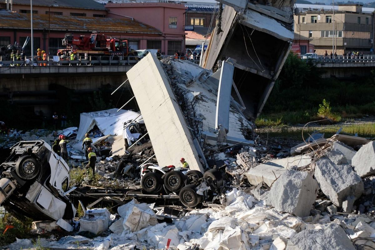 Rescuers inspect the rubble and wreckage after a section of the Morandi Bridge collapsed, on Aug 14, 2018.