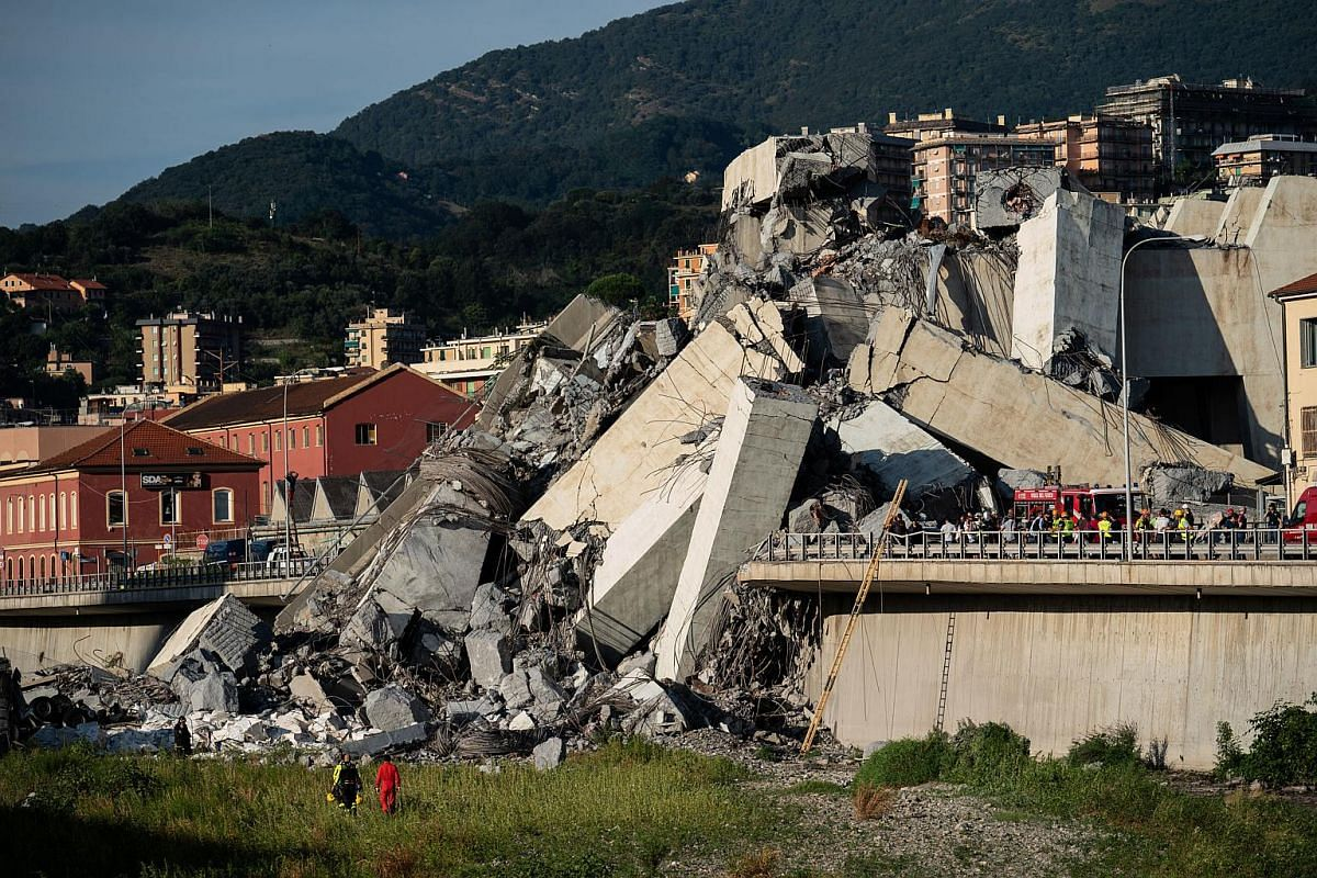 Emergency personnel search through debris from the collapsed bridge in Genoa, Italy, on Aug 14, 2018.