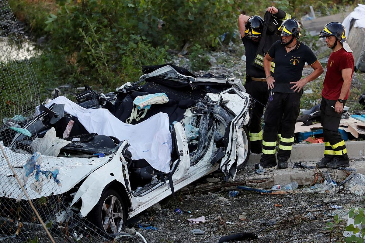 Firefighters stand next to a crushed car at the collapsed Morandi Bridge site in the port city of Genoa, Italy on Aug 14, 2018.