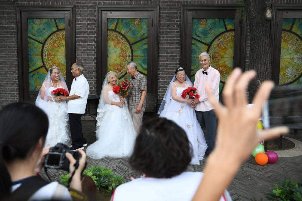 Participants pose at a photo shoot event organized to recreate wedding photos for elderly couples, who have been married for more than 50 years, a day ahead of the Qixi festival, also known as Chinese Valentine's Day, in Tianjin, China on Aug 16, 201