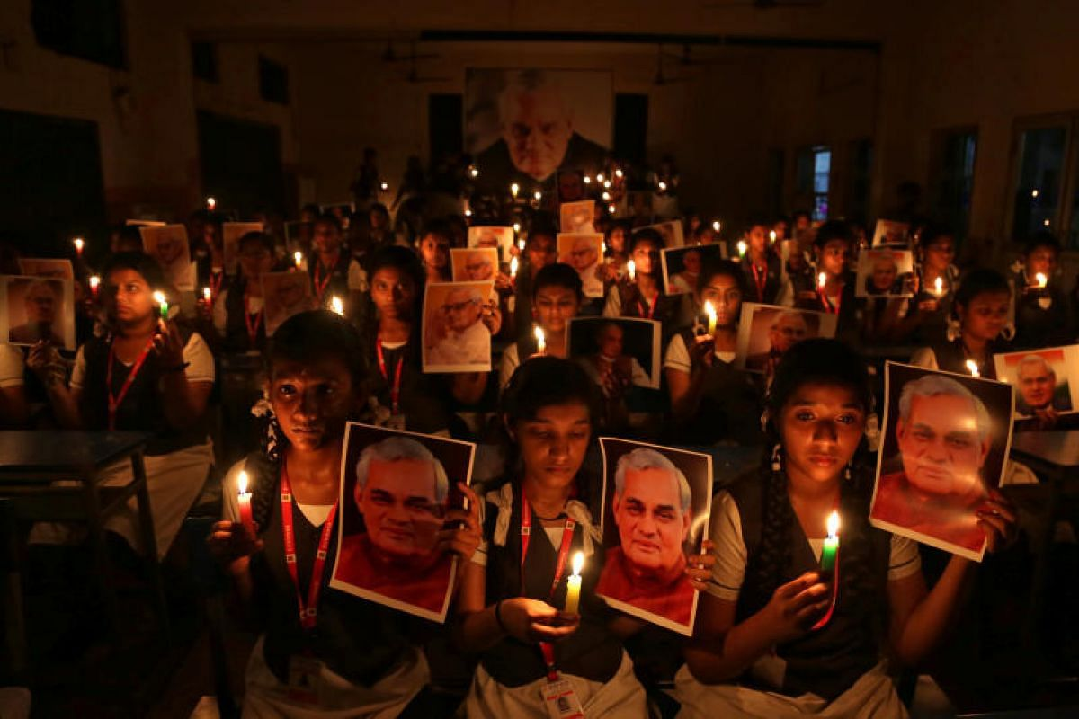 Schoolgirls hold candles and photographs of India's former prime minister Atal Bihari Vajpayee to pay him homage during a prayer ceremony inside a school in Chennai, India on Aug 16, 2018. PHOTO:REUTERS