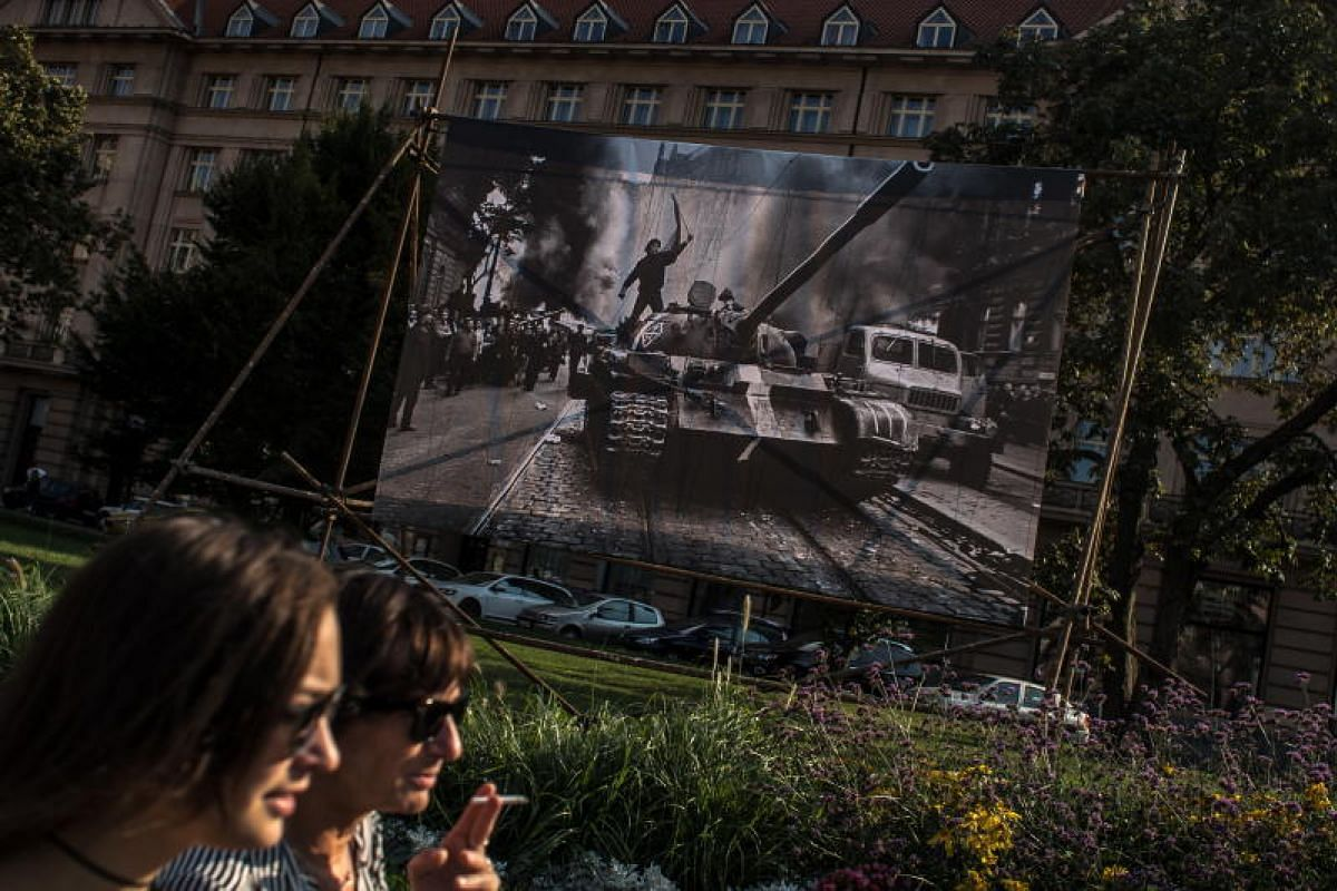 Women walk past a large photograph by Czech photographer Josef Koudelka from invasion of Warsaw Pact members in Czechoslovakia in August 1968, in Prague, Czech Republic on 16 Aug 2018. Czech people will mark on 21 August the 50th anniversary of the S