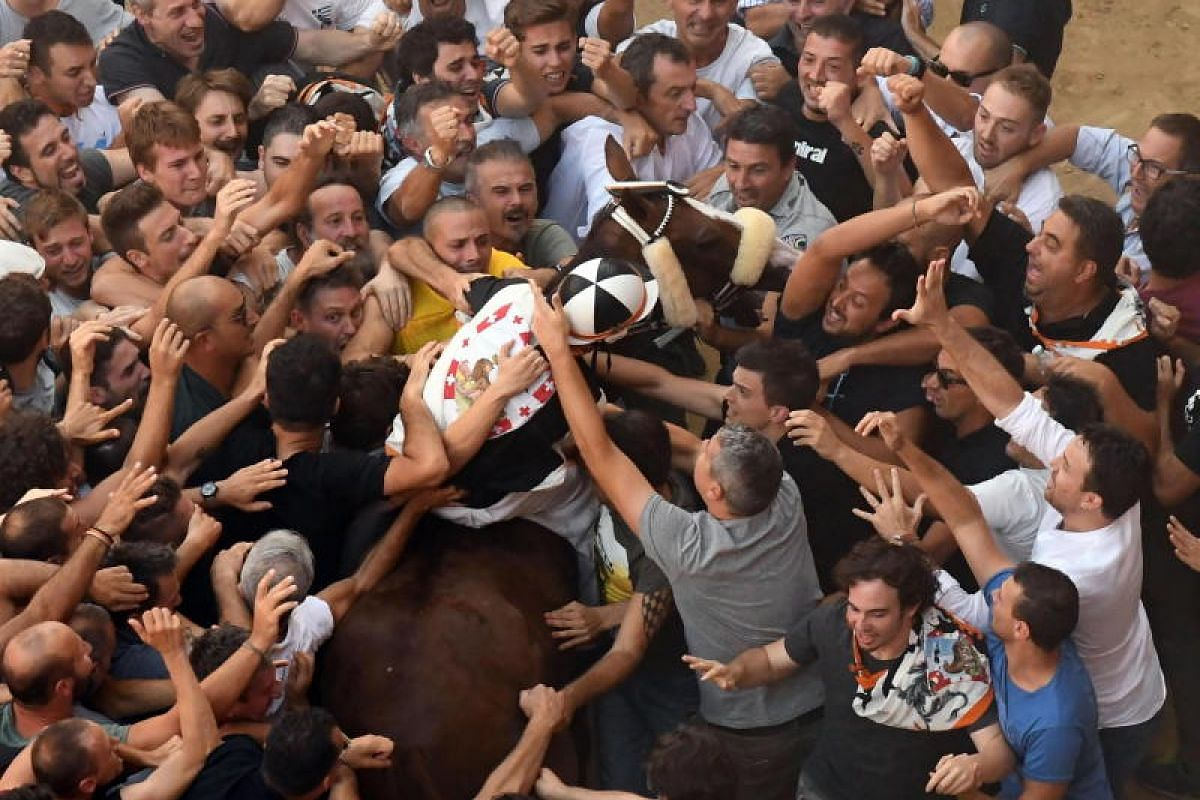 Jockey Giuseppe Zedde (C), also known as 'Gingillo' of the contrada Lupa on his horse Porto Alabe celebrates after winning the Palio di Siena (Palio dell'Assunta), in Siena, central Italy on 16 Aug 2018. The world famous horse race is dedicated to th