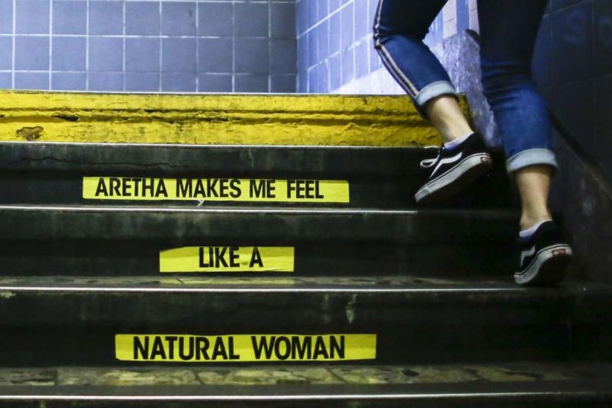 A woman exits Franklin Street Subway station while a message for Aretha Franklin is seen on the subway stairs on Aug 16, 2018 in New York. Aretha, known as the Queen of Soul, passed away in Detroit from pancreatic cancer at the age of 76. PHOTO:AFP