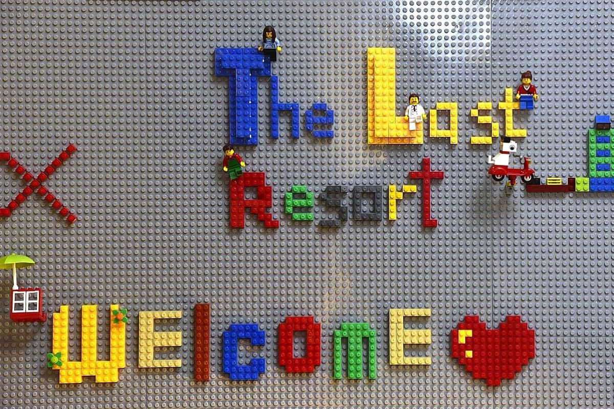 A sign in the living room made from Lego bricks. Most of the young people who come to the Thongs are from abusive and dysfunctional families. Above: The Thongs (standing) serving a meal to guests, who included residents of their home, volunteers and