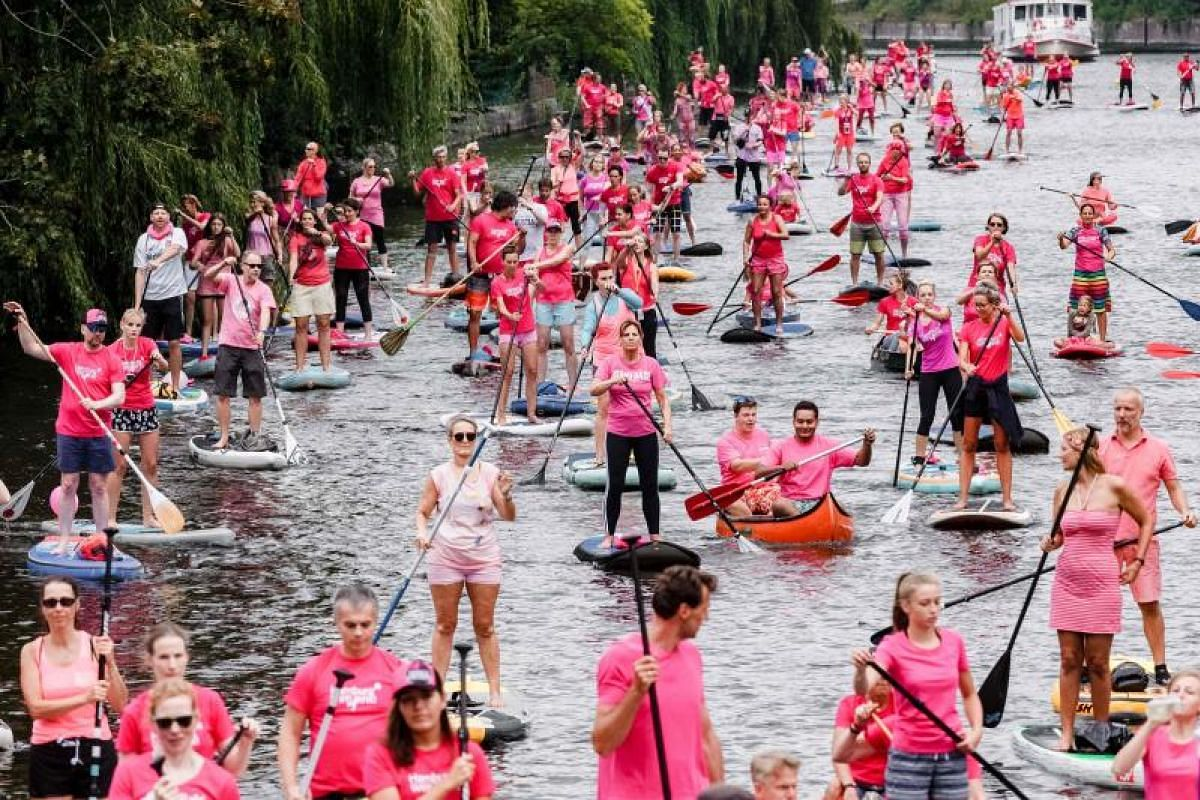 """Stand-up paddlers drive on the Alster river during the """"Hamburg's becomes pink"""" event to raise awareness for breast cancer on Aug 19, 2018 in Hamburg, northern Germany. PHOTO:AFP"""