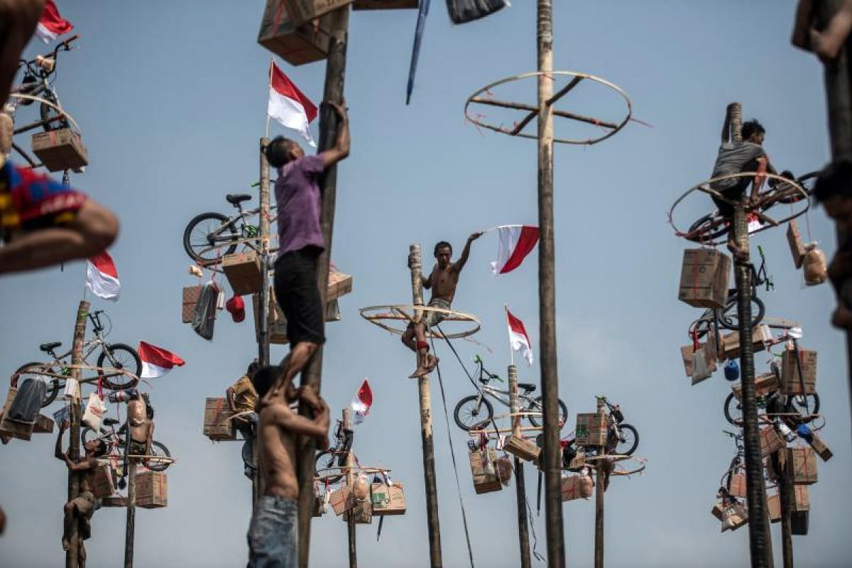 This picture taken on Aug 18, shows a man holding the Indonesia national flag during Panjat Pinang, a pole climbing contest, as part of the 2018 Asian Games festivities in Jakarta, Indonesia. Panjat Pinang, a tradition game where people place prizes
