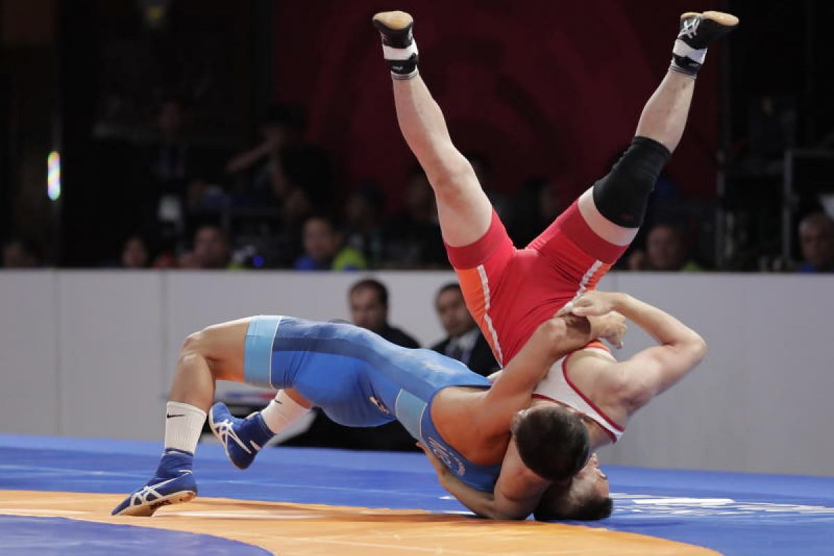 Erdenebat Bekhbayar of Mongolia(L) throws Kang Kum Song of North Korea up in the air during the Wrestling Men's Freestyle 57 kg Gold Medal competition at the Asian Games 2018 in Jakarta, Indonesia on 19, 2018. PHOTO:EPA-EFE