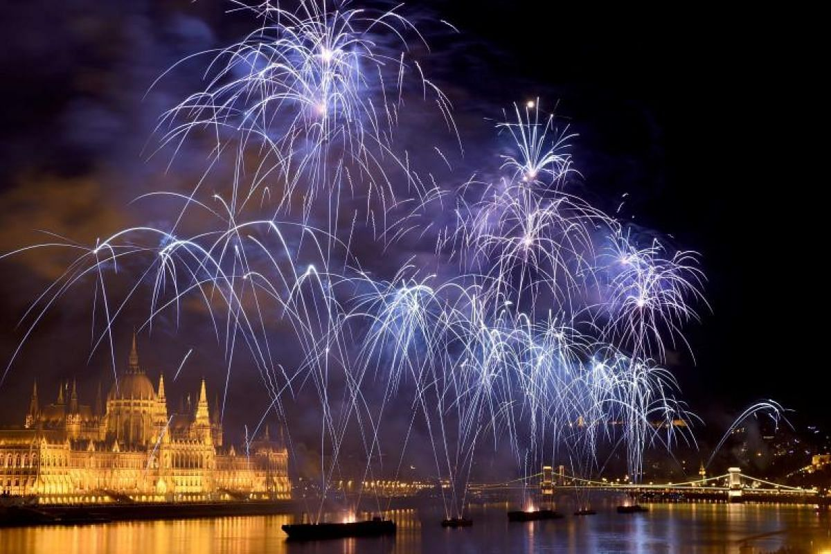 """Fireworks burst by the Hungarian Parliament building and the oldest Hungarian Bridge the """"Lanchid"""" (Chain Bridge) in Budapest on Aug 20, 2018 during the celebration of Hungary's national day. Hungary marks the 1,018th anniversary of the foundation of"""