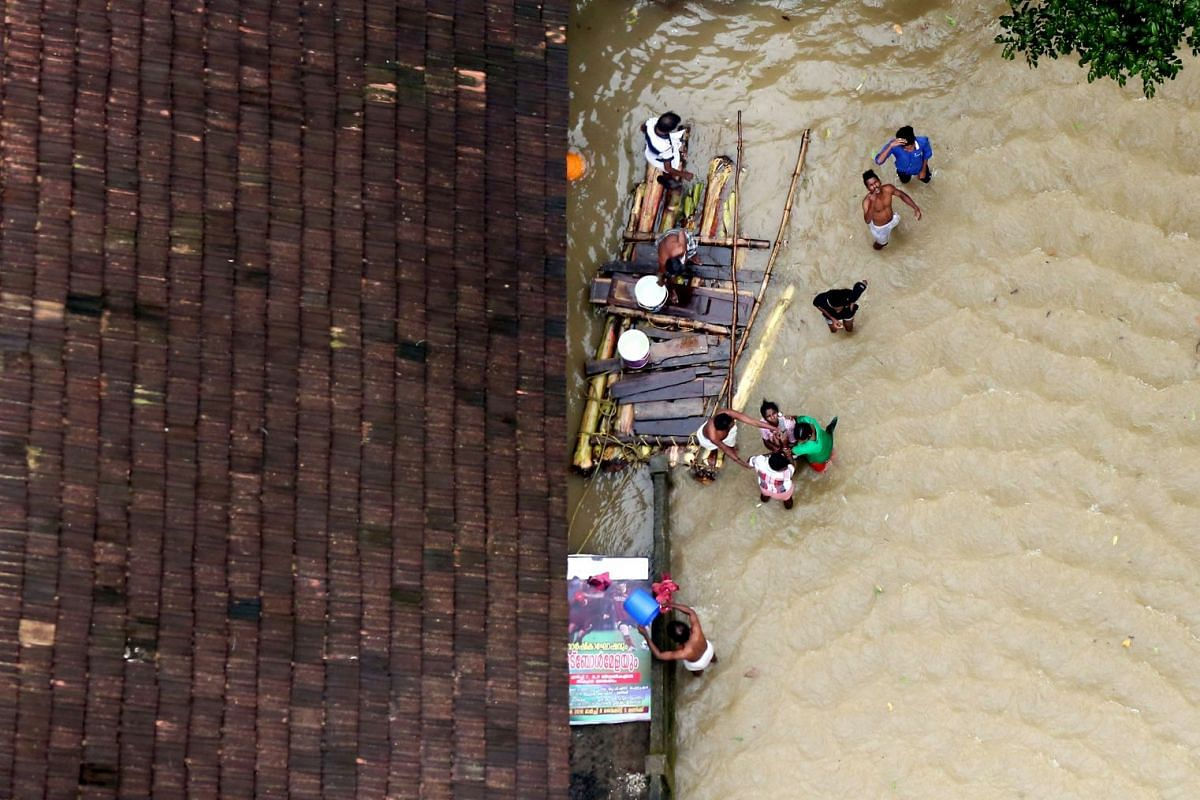 People waiting for aid next to a makeshift raft at a flooded area in the southern state of Kerala on Sunday, as the death toll from the state's worst floods in a century surpassed 400.