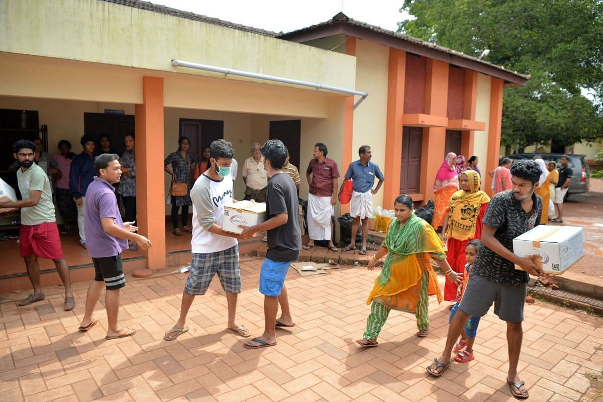 Flood victims queueing for food inside a college auditorium and volunteers (above) passing boxes of food at a relief camp for people displaced by flooding on the outskirts of Kochi.