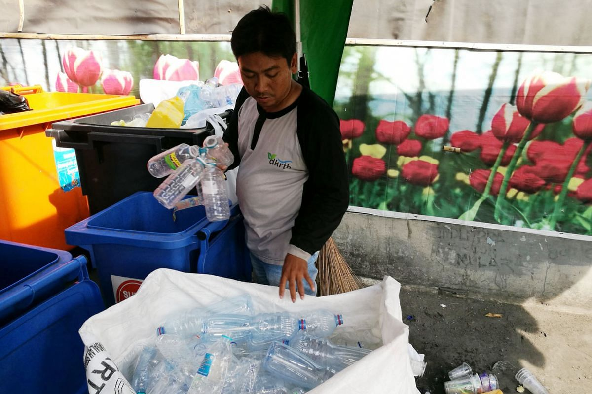 """Left: A worker (left) at a Surabaya bus terminal sorting plastic bottles according to size. Below: A passenger (below) handing over used plastic bottles and cups equivalent to her fare on a """"green"""" bus. She will get a ticket that allows her to use th"""