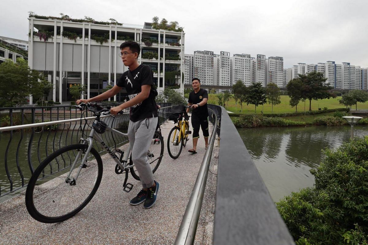 Cyclists dismount and push their bicyles across the Wave Bridge along Punggol Waterway, as neighbourhood centre Oasis Terraces (left) is seen in the background.