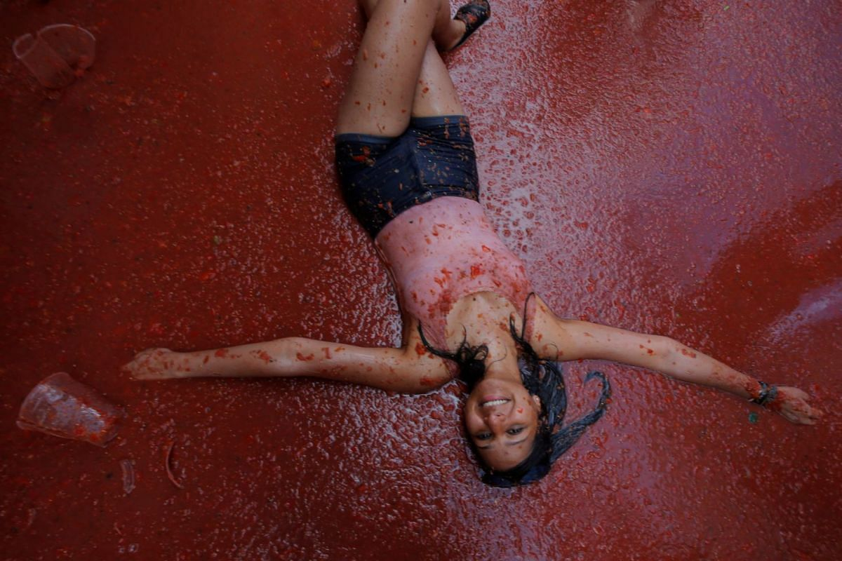 """A reveller plays with tomato pulp during the annual """"Tomatina"""" festival in Bunol, near Valencia, Spain, on Aug 29, 2018."""