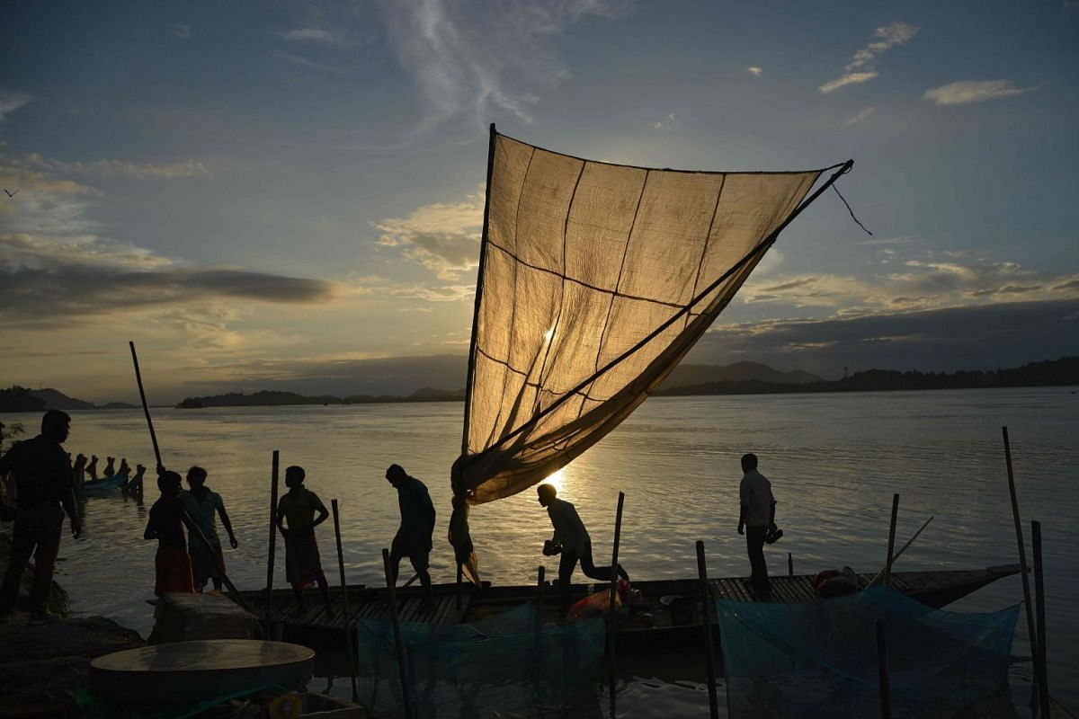 Indian fishermen load their boat with fish to sell at a market at the banks of the Brahmaputra River at Ujanbazar Ghat in Guwahati on Aug 29, 2018.