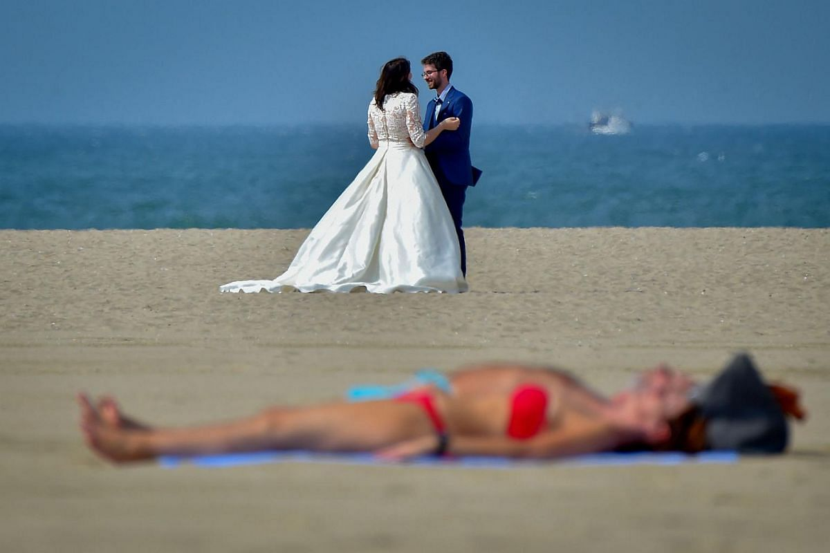 A couple pose as a sunbather lies on the beach at the Promenade des Planches during the 44th Deauville US Film Festival of Deauville in Deauville, north-western France, on Sept 3, 2018.