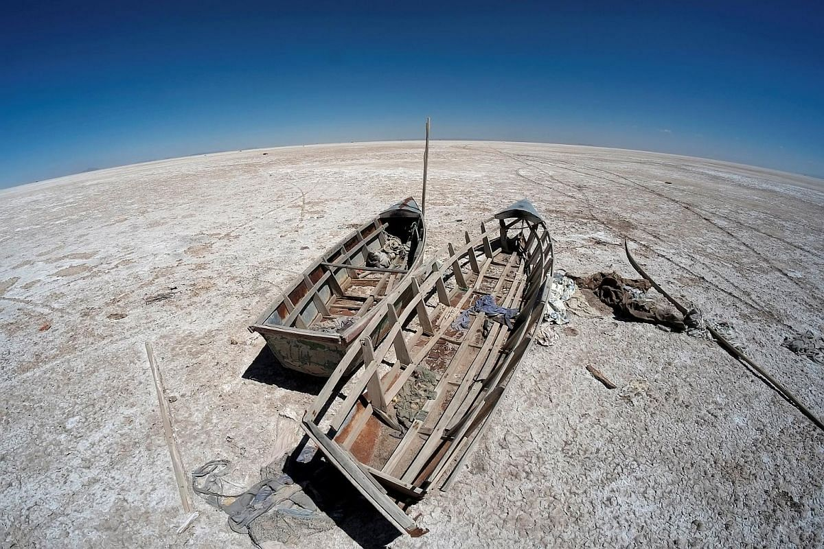 Boats are seen on the dried lake Poopo affected by climate change, in the Oruro Department, Bolivia, on Sept 1, 2017.