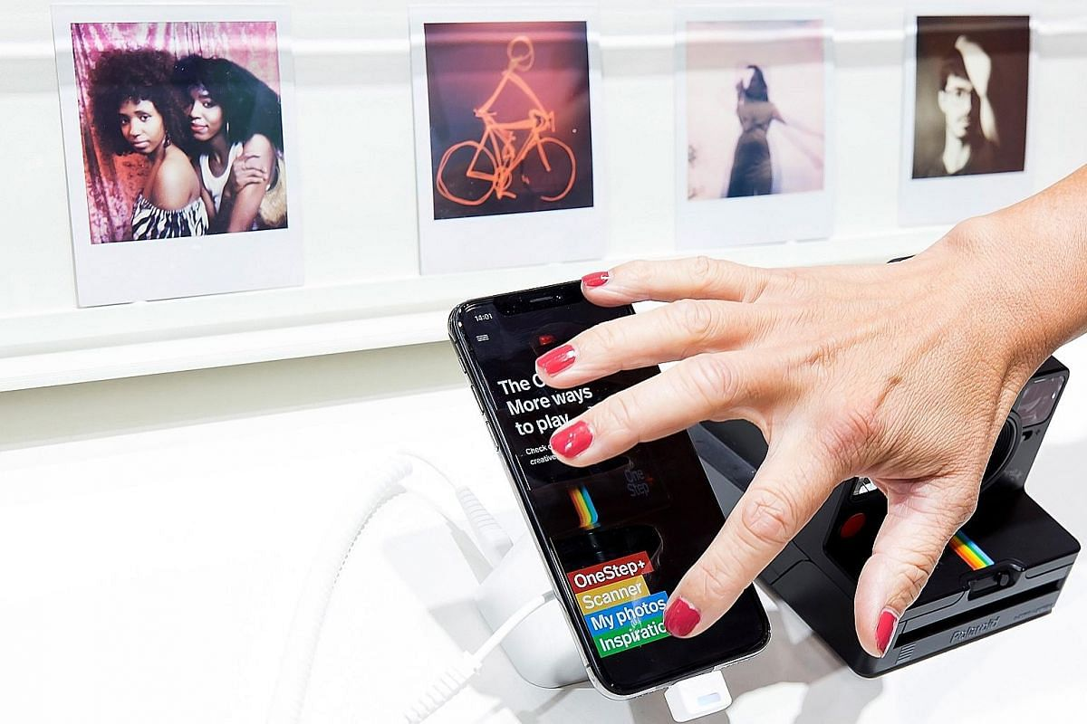 A company representative with the new Polaroid mobile phone app at the IFA trade show for consumer electronics and home appliances in Berlin, Germany, last week.