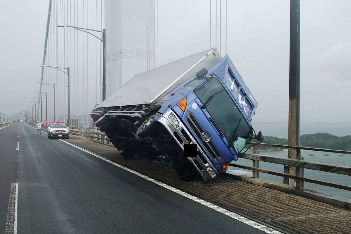 A truck lies at an angle on the Seto Ohashi bridge in Sakade, Kagawa prefecture, after being blown over by strong winds on Sept 4, 2018.