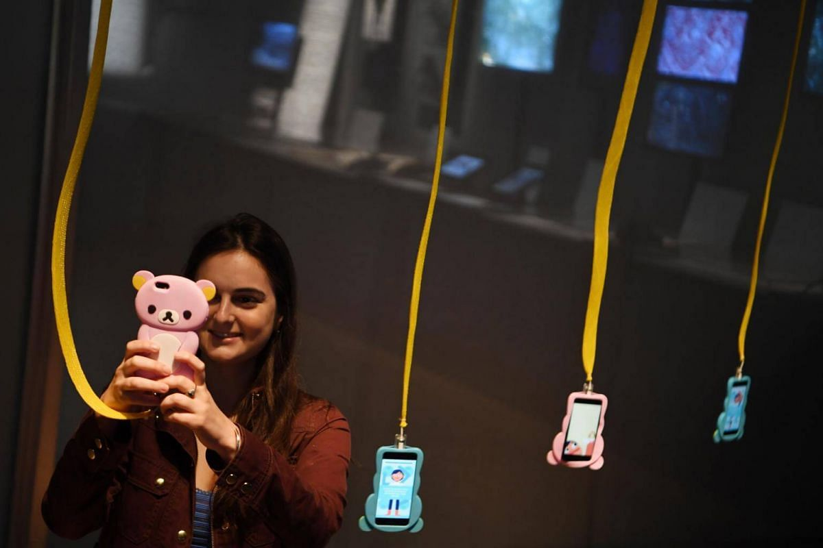 A gallery assistant plays with a computer game on a mobile device during the press preview of the exhibition, Videogames: Design/Play/Disrupt at the V&A Museum in London, on Sept 5, 2018.