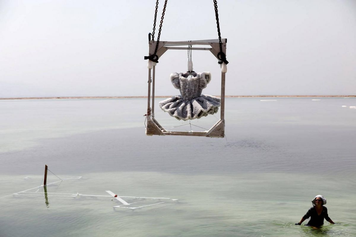 Israeli artist Sigalit Landau looks up at her artwork as it is removed from the hyper-saline waters of the southern Dead Sea, Israel, on Aug 30, 2018.