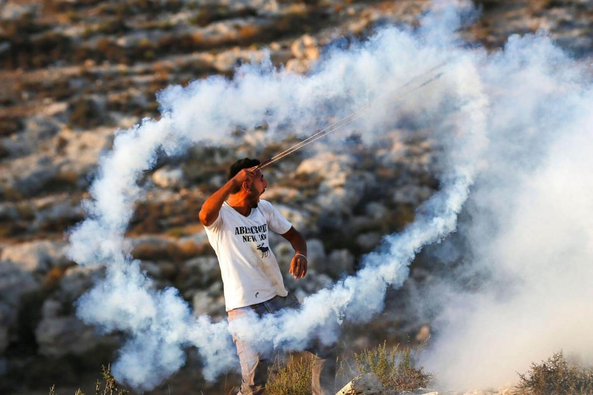 A Palestinian protester uses a slingshot to hurl back a tear gas canister towards Israeli security forces during clashes in the village of Ras Karkar, West Bank on Sept 4, 2018.