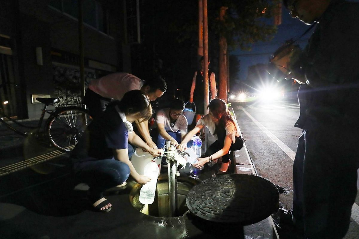 Residents fill water bottles as an electrical blackout shrouds the shopping district in Sapporo on Sept 6, 2018, after an earthquake hit the Japanese island of Hokkaido.