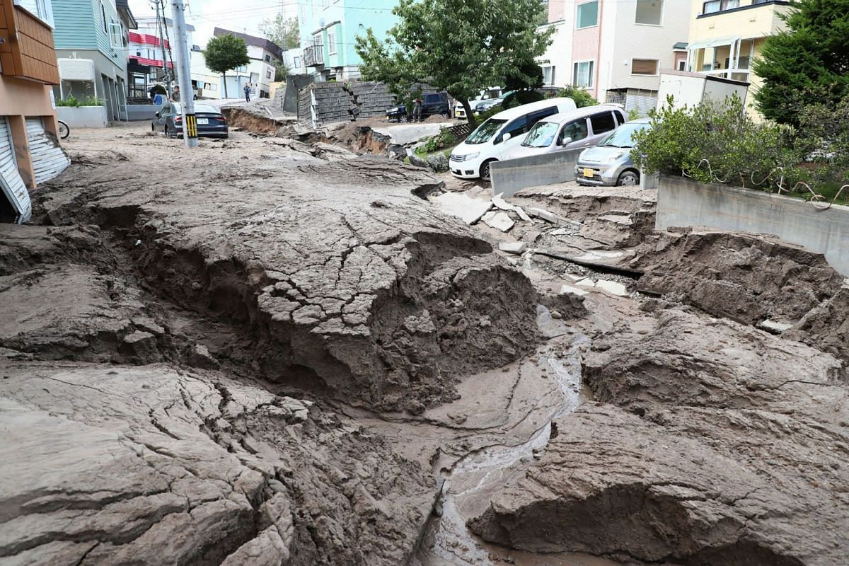 Cars are parked along a road damaged by an earthquake in Sapporo, Hokkaido prefecture on Sept 6, 2018.