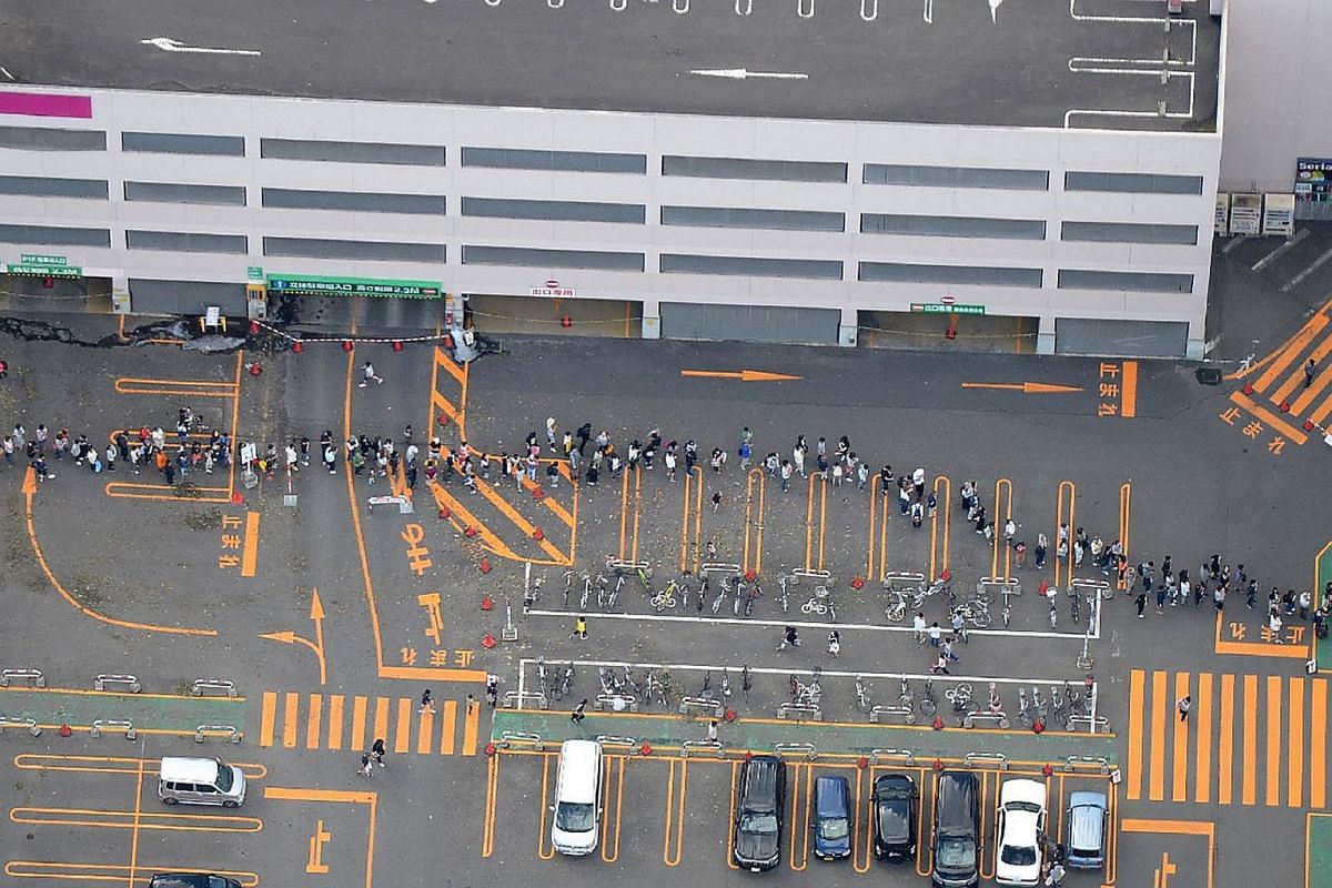 An aerial picture shows residents queueing to enter a supermarket in Sapporo, Hokkaido prefecture on Sept 6, 2018.