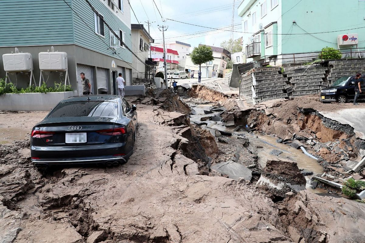A car is seen stuck on a road damaged by an earthquake in Sapporo, Hokkaido prefecture on Sept 6, 2018.