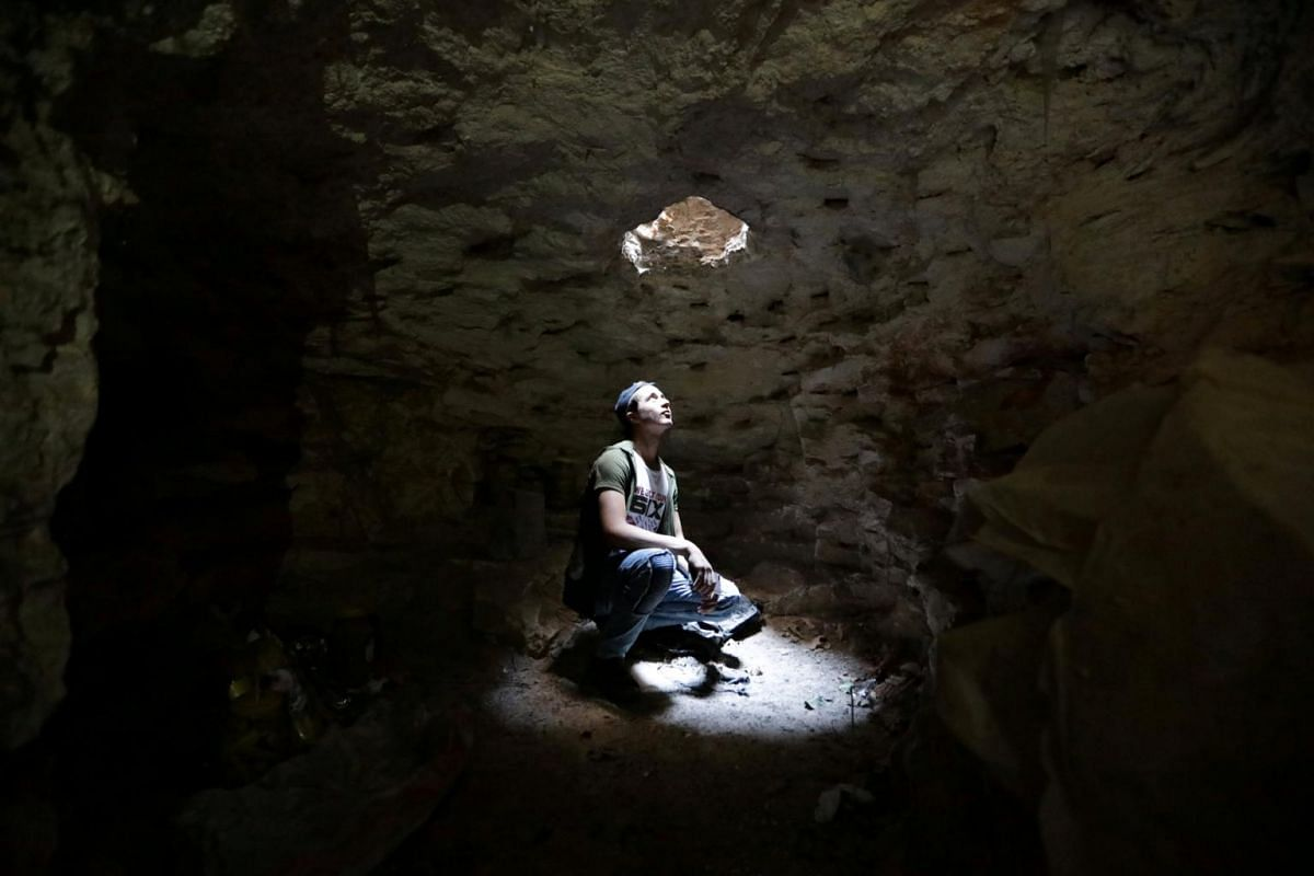 A man looks at an opening from a makeshift shelter in an underground cave in Idlib, Syria on Sept 3, 2018.