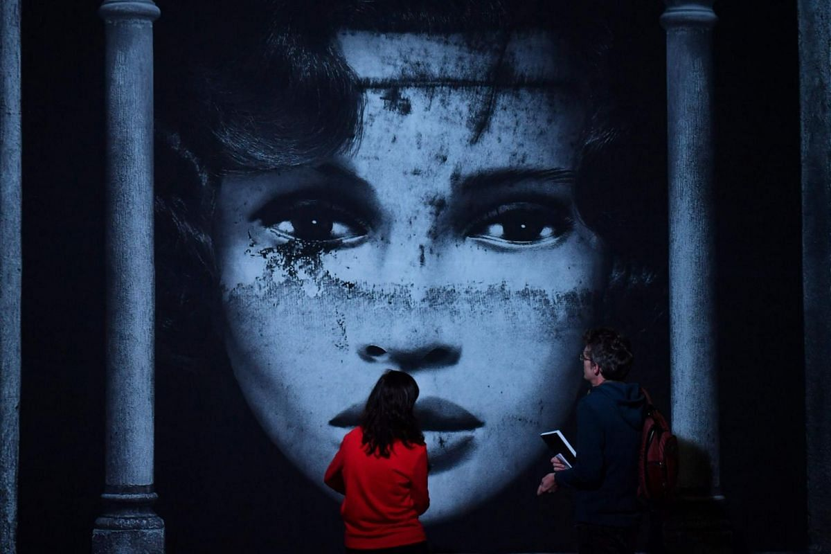People look at a street art creation displayed as part of the exhibition Strokar inside, in a former supermarket in Brussels on Sept 5, 2018, on the eve of the event's opening.