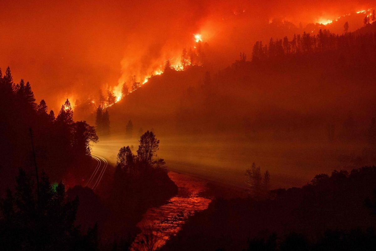 Light from a train as it rounds a bend near the Sacramento River as flames from the Delta Fire fill a valley in Delta, California on Sept 6, 2018.