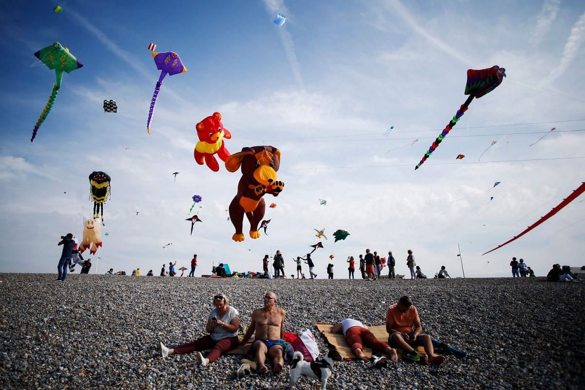 People fly kites on a beach while others sunbathe during the 20th edition of the International Dieppe Kite Festival on Sept 9, 2018 in Dieppe, northwestern France. PHOTO: AFP