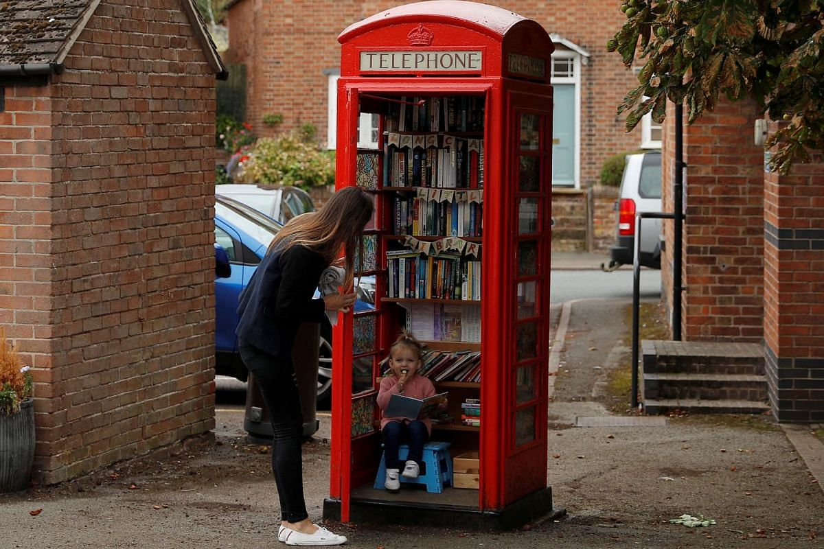 Aria Casey aged 2 looks at books in a library inside a former British Telecom phone box in Long Clawson, Britain September 10, 2018. REUTERS