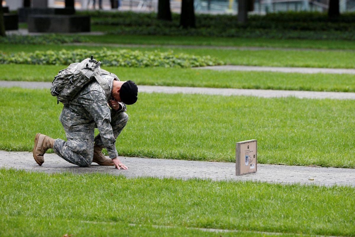 US Army Reserve Sgt Edwin Morales kneels as he honours his cousin Ruben Correa during ceremonies marking the 17th anniversary of the Sept 11, 2001 attacks on the World Trade Center, at the National 9/11 Memorial and Museum in New York on Sept 11, 201