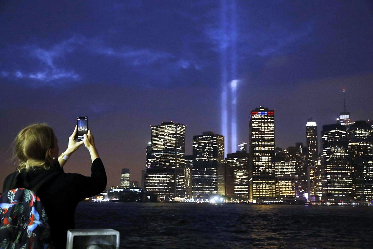 A spectator records the Tribute in Light installation with her mobile phone as it is illuminated over lower Manhattan as seen from Brooklyn, marking the 17th anniversary of the 9/11 attacks in New York City, on Sept 11, 2018.