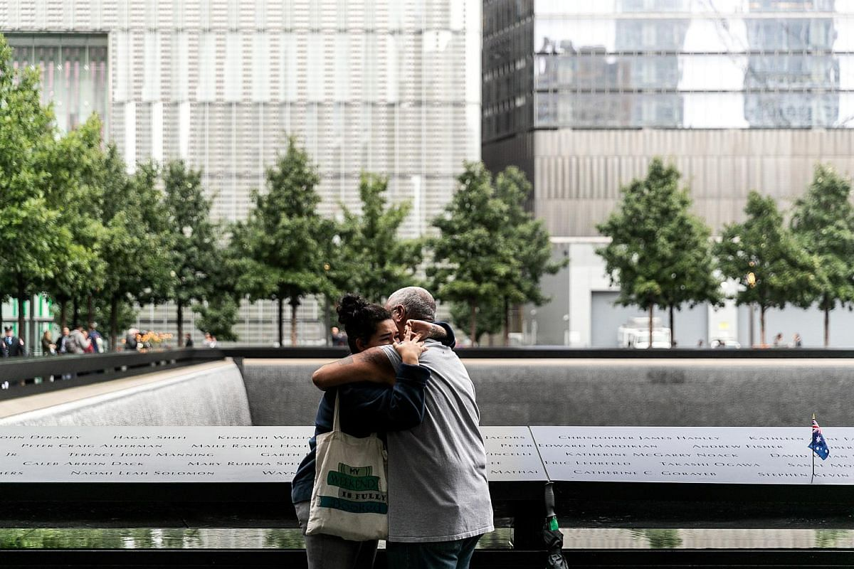 Visitors embrace at the National Sept 11 Memorial & Museum on the 17th anniversary of the 9/11 attacks.