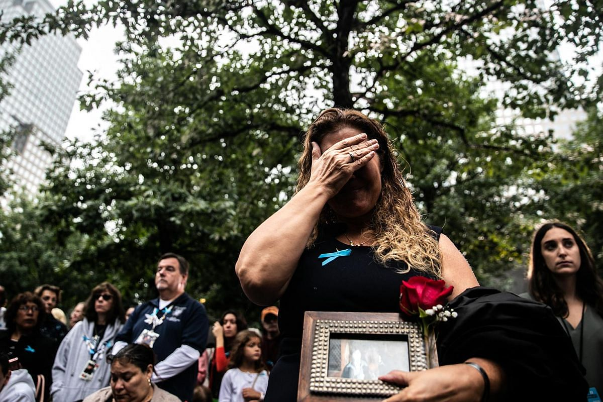 An attendee cries during a ceremony marking the 17th anniversary of the 9/11 attacks, at the National 9/11 Memorial and Museum in New York, on Sept 11, 2018.