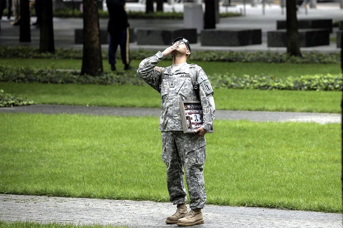 Army Reserve Sgt. Edwin Morales blows a kiss skyward in memory of his late friend Ruben Correa, a firefighter who died in the 9/11 attacks, before the start of a commemoration ceremony for the victims of the terrorist attacks.