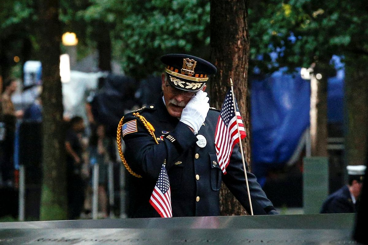 A guest wipes a tear among names at the edge of the south reflecting pool at the National 9/11 Memorial and Museum during ceremonies marking the 17th anniversary of the 9/11 attacks on the World Trade Center in New York, on Sept 11, 2018.